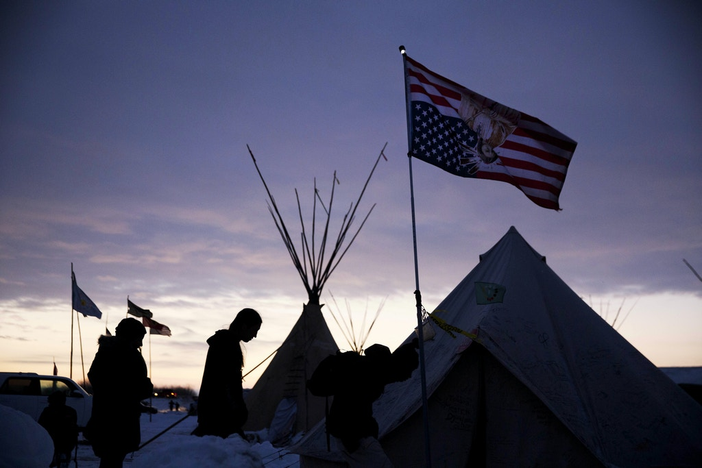 FILE - In this Dec. 4, 2016 file photo, travelers arrive at the Oceti Sakowin camp where people have gathered to protest the Dakota Access oil pipeline as they walk into a tent next to an upside-down american flag in Cannon Ball, N.D. It has been called the largest gathering of Native American tribes in a century. Tribal members and others have joined in an ongoing, tense protest against the $3.8 billion Dakota Access oil pipeline, which the Standing Rock Sioux believes threatens sacred sites and a river that provides drinking water for millions of people. The protest is included in the AP top news stories in North Dakota this year. (AP Photo/David Goldman File)