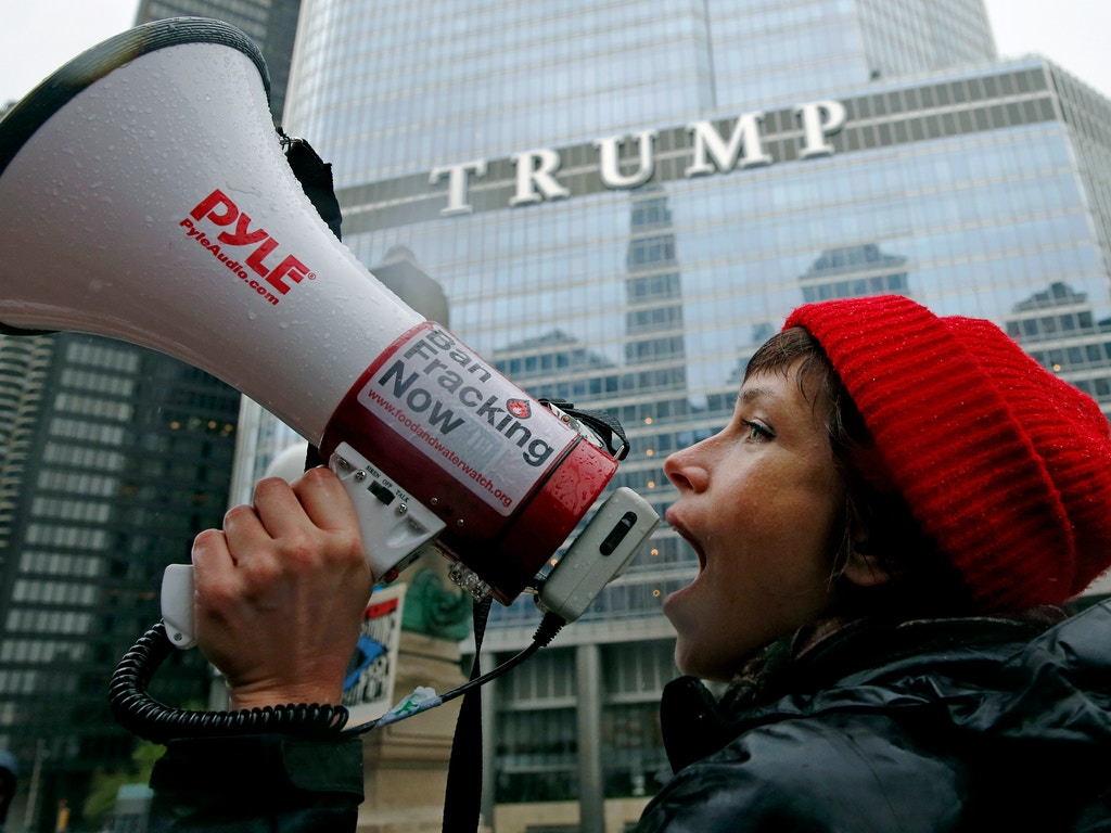 "Jessica Fujan chants on the Wacker Drive during a ""100 Days of Failure"" protest and march, Saturday, April 29, 2016, in Chicago. Thousands of people across the U.S. are marking President Donald Trump's hundredth day in office by marching in protest of his environmental policies. (AP Photo/Nam Y. Huh)"