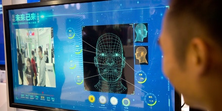 A man watches as a visitor tries out a facial recognition display at a booth for Chinese tech firm Ping'an Technology at the Global Mobile Internet Conference (GMIC) in Beijing, Thursday, April 26, 2018. The GMIC features current and future trends in the mobile Internet industry by some major foreign and Chinese internet companies. (AP Photo/Mark Schiefelbein)