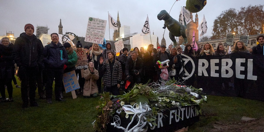 Environmental activists gather around a mock 'coffin' with