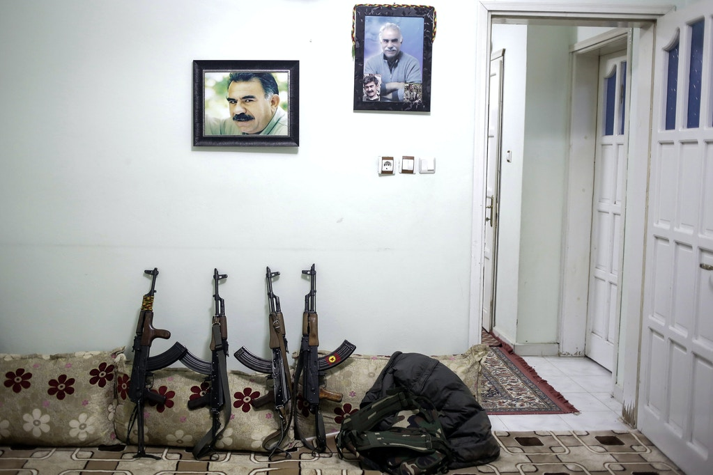 NUSAYBIN, TURKEY -  FEBRUARY 25: AK-47's of armed group Patriotic Revolutionary Youth Movement (YDG-H), a youth division of the Kurdistan Workers' Party, PKK, stand under jailed Kurdish rebel leader Abdullah Ocalan's pictures in a house in southeastern Turkish city of Nusaybin on February 25, 2016, Turkey. Since mid-December, the Turkish security forces placed to several predominantly Kurdish cities in Turkey under 24-hour martial law and curfew on the premise of restoring public order. (Photo by Cagdas Erdogan/Getty Images)