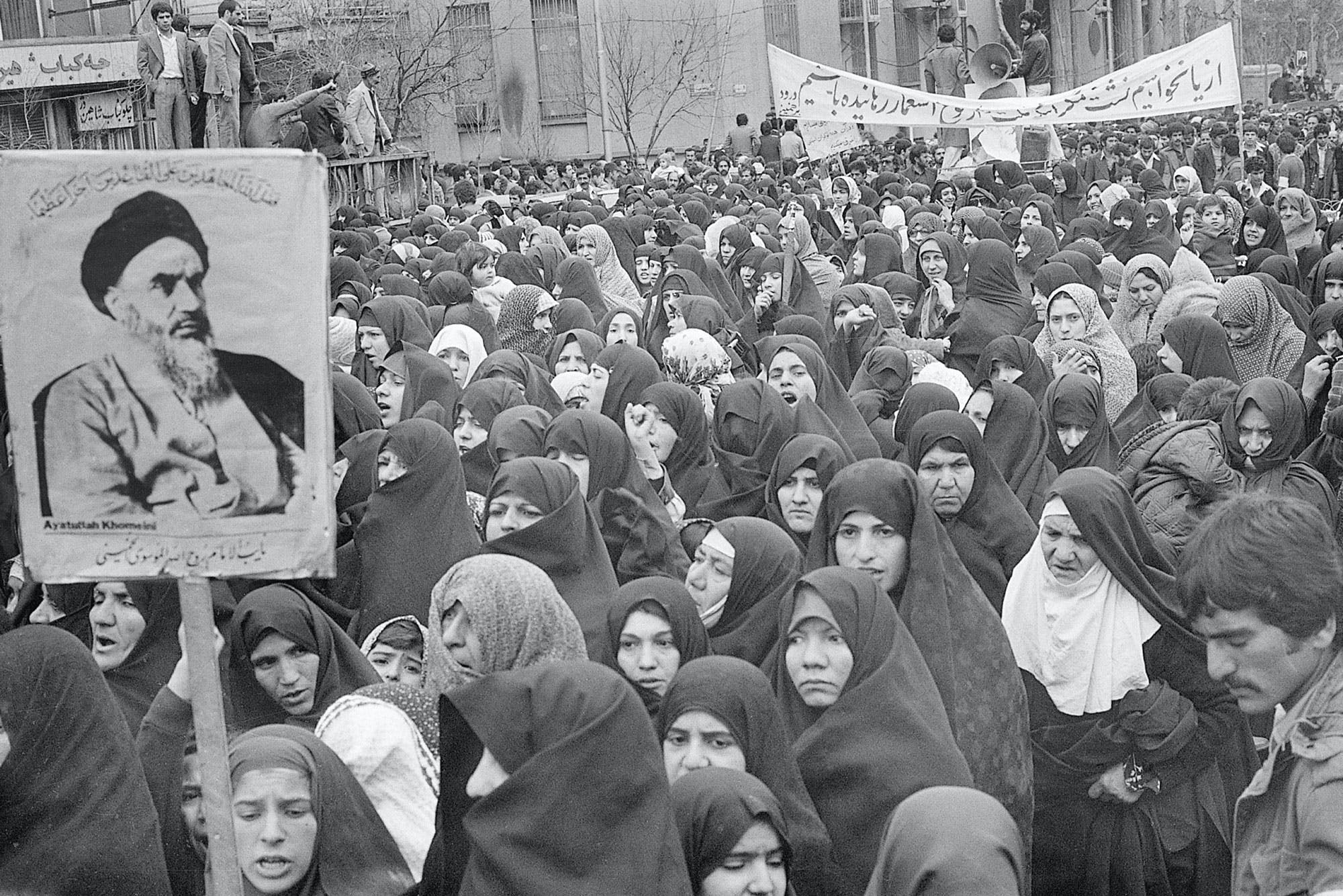 (Original Caption) 2/1979-Tehran, Iran- Women dressed in traditional Moslem garb are gathered near a sign bearing an image of the Ayatollah Khomeini, during a Tehran rally early in Februaury... Khomeini has called for all women to wear the traditional head-to-ankle chador. Wearing western style dress and makeup and smoking, women took to the streets in a series of marches. Several thousand Pro-Khomeini women, many covered by the veil, staged a counter-demonstration.
