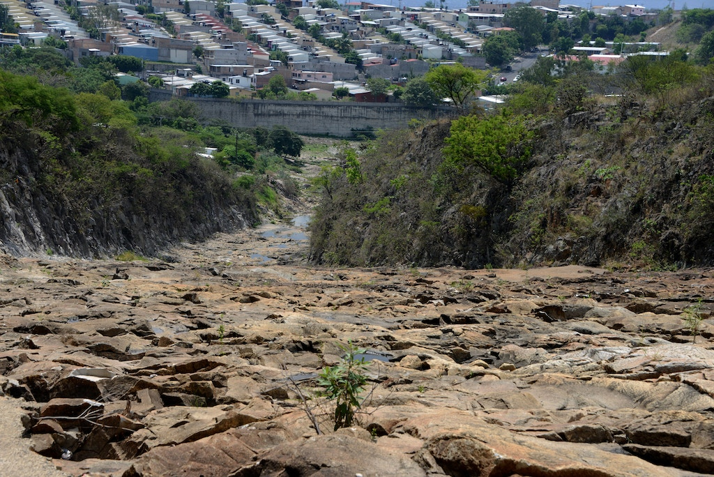 A view of a neighborhood behind a dried-up portion of the Los Laureles reservoir, which along with the La Concepcion and El Picacho reservoirs supplies the Honduran capital Tegucigalpa and its twin city Comayaguela, seen on May 26, 2016.  Due to the lengthy drought plaguing Honduras, which has been exacerbated by the El Nino climate phenomenon, the water and sewerage utility SANAA is about to declare a state of emergency in the Honduran capital.  / AFP / ORLANDO SIERRA        (Photo credit should read ORLANDO SIERRA/AFP/Getty Images)