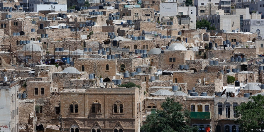 A picture taken on June 29, 2017 shows a view of the houses in the old town of the divided city of Hebron in the southern West Bank.On July 7, 2017 UNESCO declared in a secret ballot the Old City of Hebron in the occupied West Bank a protected heritage site.Hebron is home to more than 200,000 Palestinians, and a few hundred Israeli settlers who live in a heavily fortified enclave near the site known to Muslims as the Ibrahimi Mosque and to Jews as the Cave of the Patriarchs. / AFP PHOTO / HAZEM BADER (Photo credit should read HAZEM BADER/AFP/Getty Images)