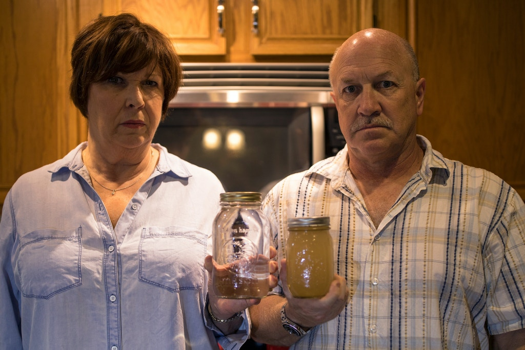 WEST WHITELAND, PENNSYLVANIA - OCTOBER 6: Homeowners Diane Salter, left, and David Mano, right, hold two jars with undrinkable clear and clouded well water caused by Sunoco's drilling for a natural gas liquids pipeline that contaminated their residential well October 6, 2017 in West Whiteland, Pennsylvania. Sunoco's horizontal drilling for their 350-mile Mariner East 2 pipeline project goes through Mano's and Slater's backyard and will eventually terminate in Sunoco's Marcus Hook Industrial Complex in on the Delaware coast for export. (Photo by Robert Nickelsberg/Getty Images)