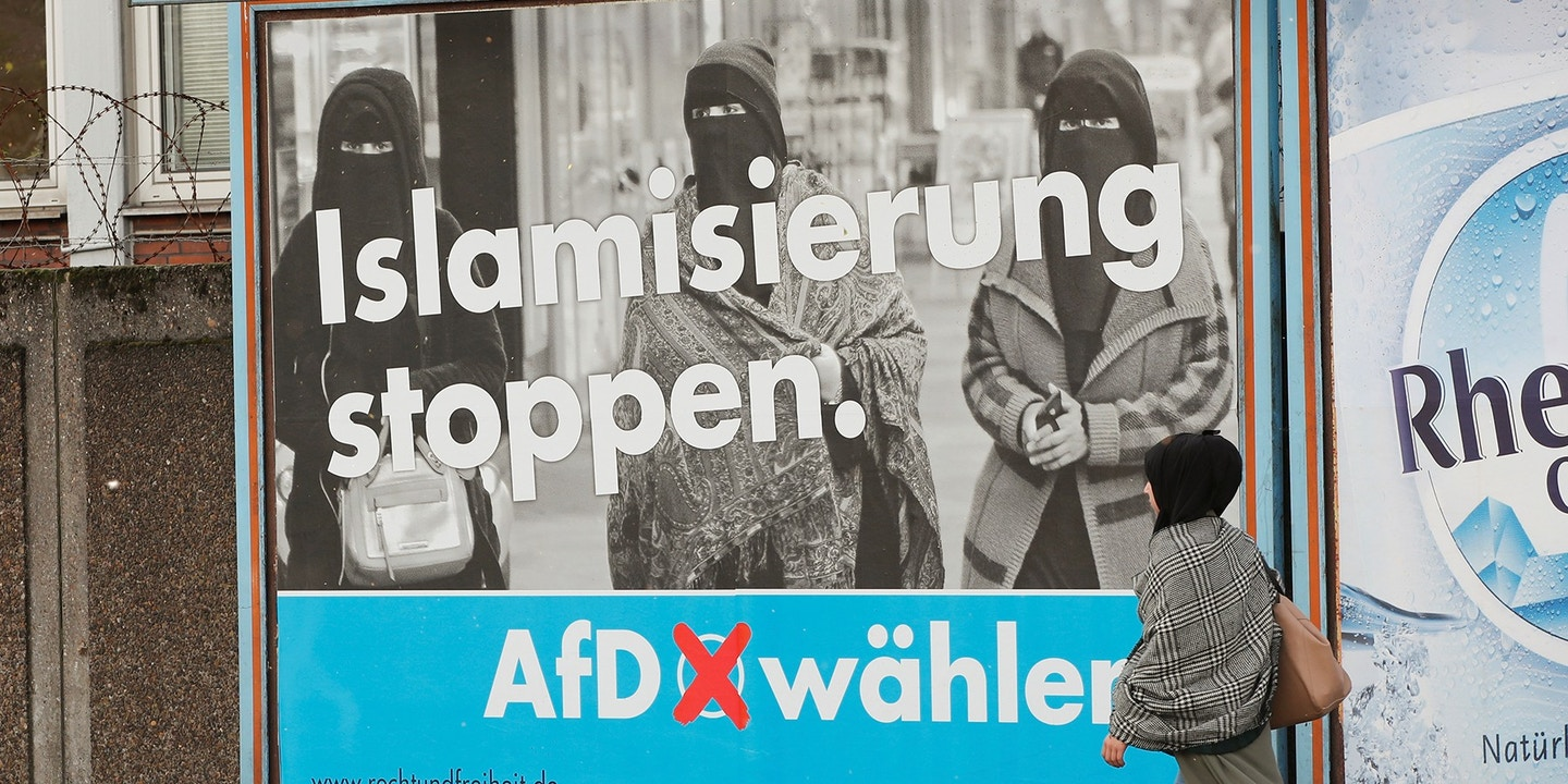 A woman with a headscarf walks past an election campaign poster of the anti-immigration party Alternative fuer Deutschland AfD, in Marxloh, a suburb of Duisburg which local media said is populated mostly with people of Turkish migrant background, Germany September 13, 2017. REUTERS/Wolfgang Rattay - RC1E121F7220