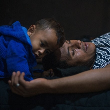 Eric and Julian rest on a bed after months of sleeping in tents at the Hotel Belen, on December 9, 2018.