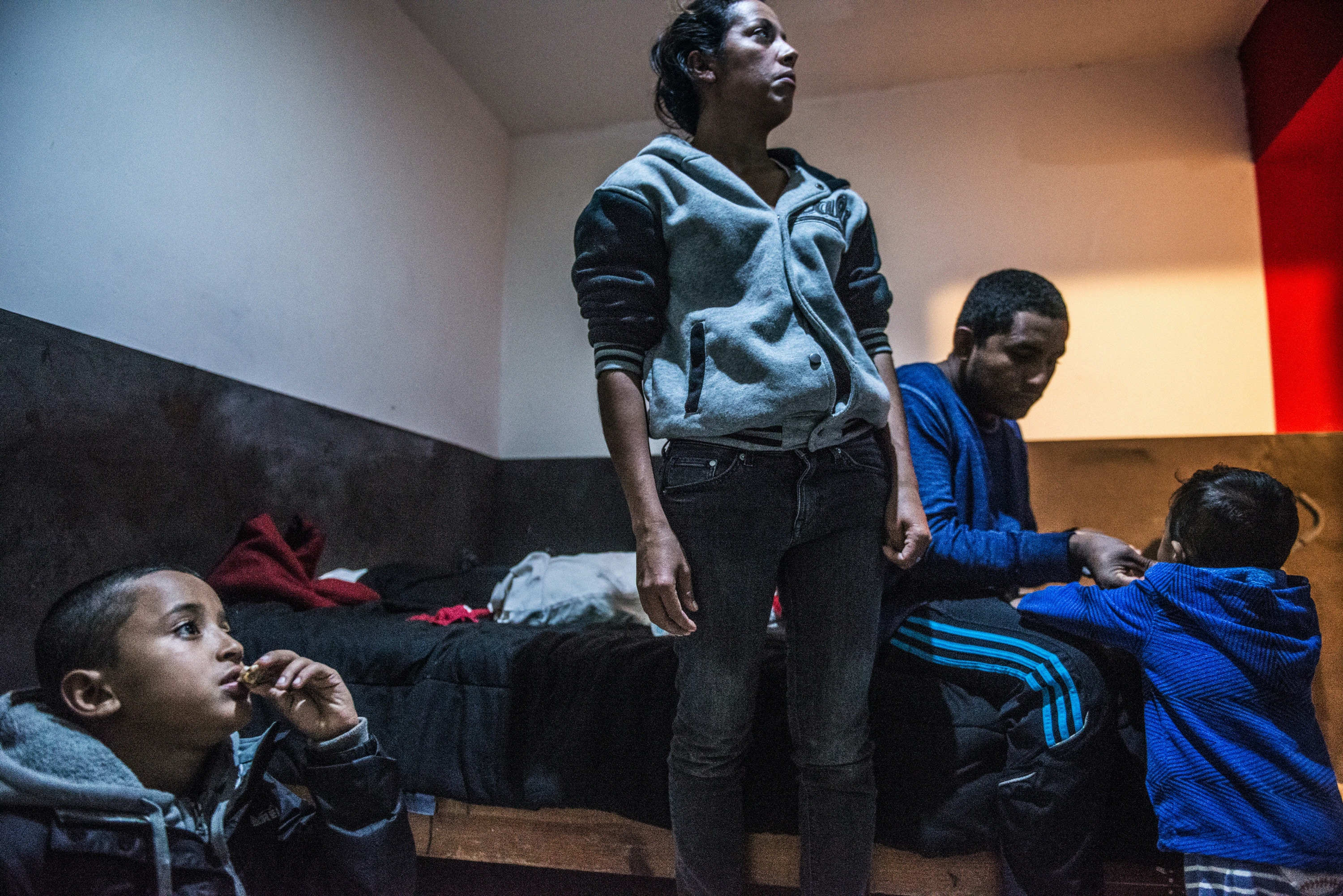 Kelvin and Oneida watch news on television about the Central American Exodus while Eric and Julian play in the background in their room at Hotel Belen, on December 9, 2018.