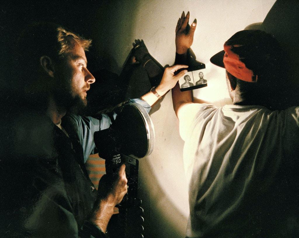 """Um oficial de justiça, à esquerda, mostra uma foto de um suspeito a um homem que, segundo a polícia, fora encontrado usando drogas em um ponto de venda de entorpecentes em Washington, D.C., no dia 18 de julho de 1989. A operação fazia parte da """"guerra às drogas"""" do então presidente dos EUA, George H. W. Bush."""