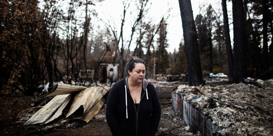 """Michelle's Teixeira at the rubble of her home that burned in the Camp Fire, Paradise, California, December 21st, 2018. Michelle Teixeira is living in a 300 square foot trailer with her husband, her father, two daughters, and four dogs. Her husband's boss owns a residential development made up of 36 empty lots, where the Teixeiras and five other families have made camp, calling themselves the """"trailer treasures."""" They're all refugees from the Camp wildfire, which leveled Paradise, California, killing 86 people, including many retirees.Talia Herman for The Intercept"""
