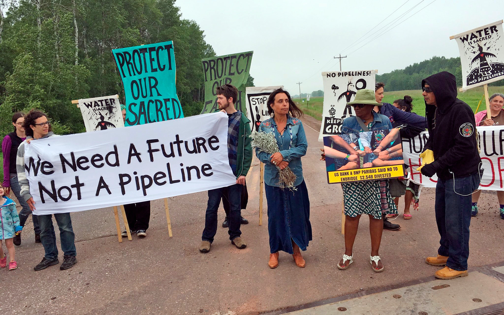Winona Laduke? and others demonstrate at a rally held at the Wisconsin-Minnesota border on the morning after Line 3 is approved, Friday, June 29, 2018. They're vowing to fight to keep the oil pipeline from being built across Minnesota. The Minnesota Public Utilities Commission on Thursday determined the project is necessary and approved the Canadian company's preferred route across northern Minnesota, with modifications and conditions that Enbridge considers minor. (Dan Kraker/Minnesota Public Radio via AP)