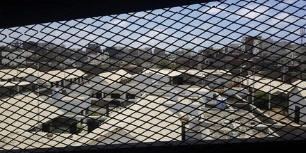 FILE - This May 9, 2017 file photo, shows a view through a mesh window over part of Aden Central Prison, known as Mansoura, in Aden, Yemen. A section of the prison is run by Yemeni allies of the United Arab Emirates, part of a network of secret prisons in southern Yemen. Yemen's deputy interior minister said secret prisons that the AP had reported are under the control of the United Arab Emiratis and its allied militias are now under the authority of the Yemeni government. However, other security officials contradicted the statement Monday, July 9, 2018, by Maj. Gen. Ali Lakhsha. (AP Photo/Maad El Zikry, File)