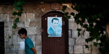 In this Wednesday, July 18, 2018, photo, a poster of Syrian President Bashar Assad is displayed on the door of a souvenir store in the Takiyya complex in the old town of Damascus, Syria. His face is everywhere. Buoyed by successive military advances in the past year and having completely secured his seat of power and surrounding suburbs for the first time in years, Assad's government is openly boasting about its victories with posters and billboards placed on every public square, market and street corner. (AP Photo/Hassan Ammar)