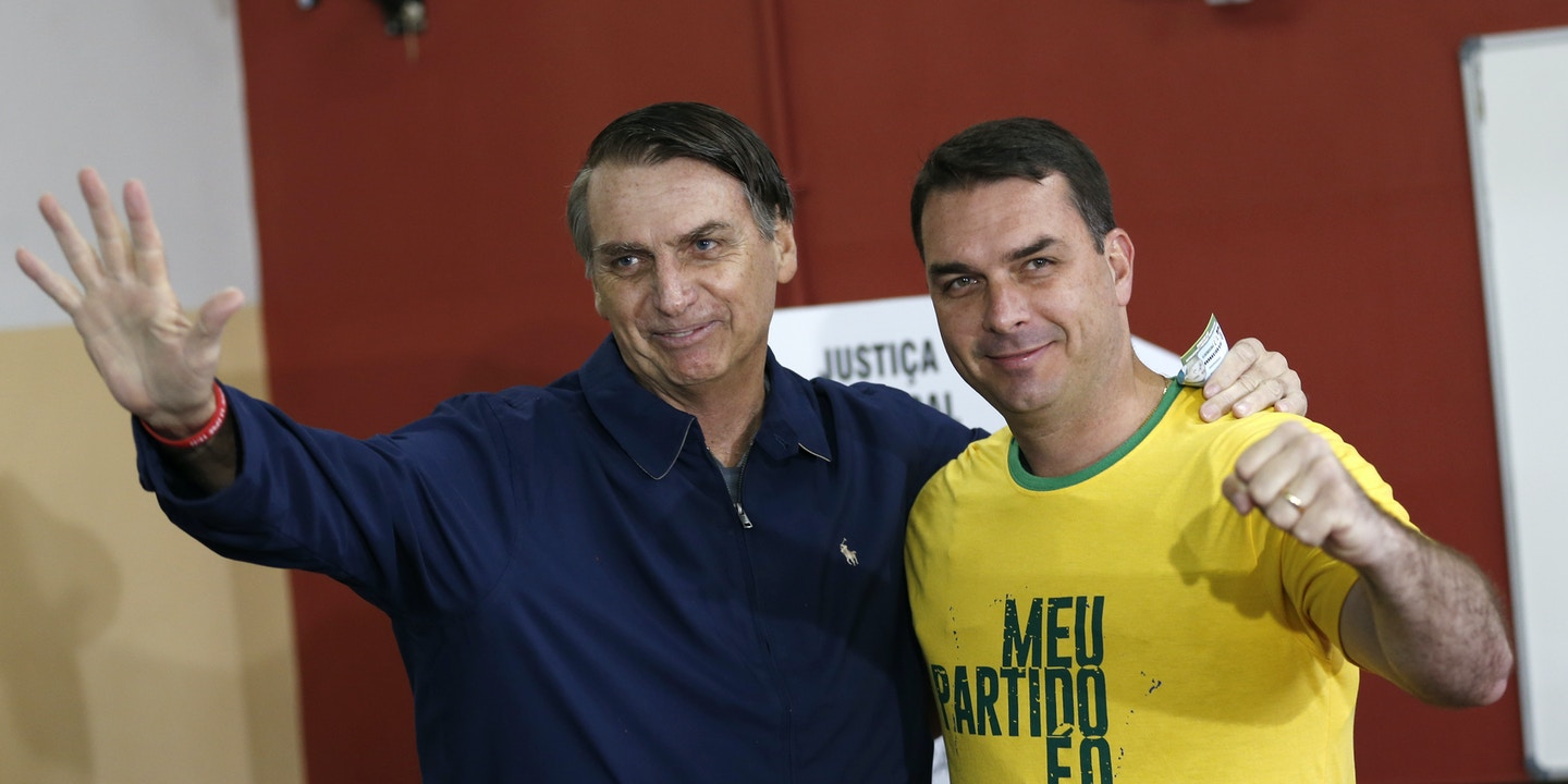 """FILE - In this Oct. 7, 2018 file photo, then presidential frontrunner Jair Bolsonaro, left, and his son Flavio, acknowledge reporters at a polling station in Rio de Janeiro, Brazil. The son of Brazilian President-elect Jair Bolsonaro is denying wrongdoing in a case involving suspect bank transactions. According to a recent Financial Activities Control Council report, Flavio Bolsonaro's driver deposited various amounts between January 2016 and January 2017. On Thursday, Dec. 13, 2018, Flavio Bolsonaro posted on Twitter that he had """"done nothing wrong."""" (AP Photo/Silvia Izquierdo, File)"""