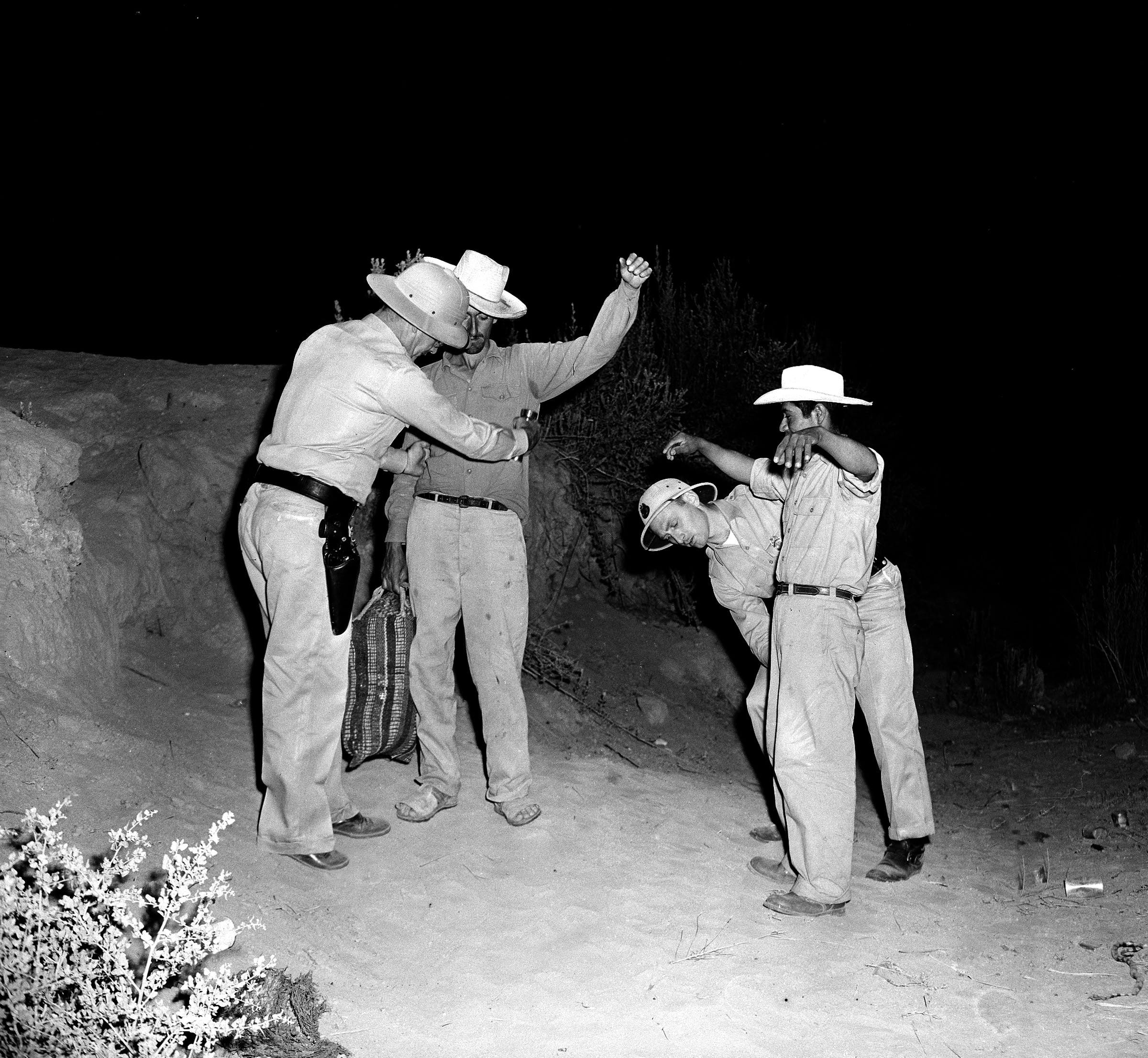 U.S. Border Patrol inspectors Fred H. Voight, left, and Gordon MacDonald, right, both from the El Centro U.S. Border Patrol sector headquarters, are searching two Mexican nationals, Pedro Vidal, with bag, and Canuto Garcia, right, shortly after the two men illegally crossed the border from Mexico, west of Calexico, Calif., August 11, 1951. Thousands of Mexican laborers are trying to cross in this area into the United States, where they attempt to work on the farms of the nearby Imperial Valley. (AP Photo)