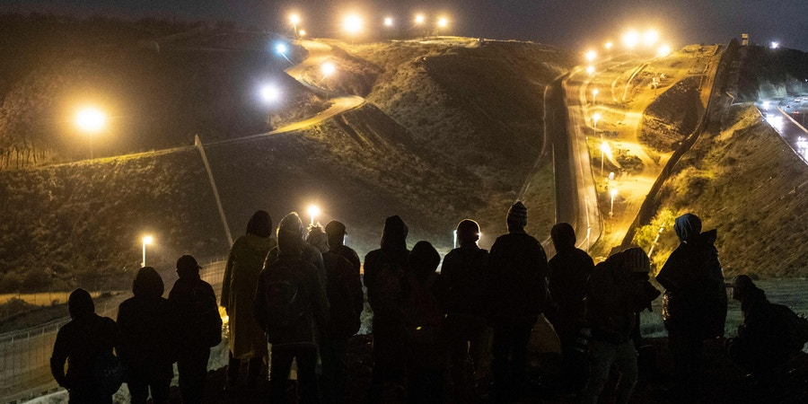 TOPSHOT - Central American migrants stand on a mound before attempting to cross from Tijuana to San Diego in the US on New Year's Eve, as seen from Tijuana, Baja California state, Mexico on December 31, 2018. - Around 100 Central American migrants made a failed attempt on New Year's Eve to cross over from Mexico into the United States. As night fell and people on both sides of the frontier prepared to celebrate New Year's Eve, the migrants tried to cross over but at least two smoke bombs were hurled and they ultimately held back. (Photo by Guillermo Arias / AFP)        (Photo credit should read GUILLERMO ARIAS/AFP/Getty Images)