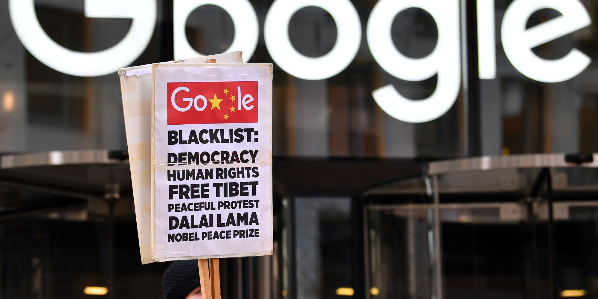 """A demonstrator holds a placard as they protest outside the offices of Google in London on January 18, 2019. - A global coalition of 60 human rights and media groups wrote to Google chief executive Sundar Pichai urging him to scrap the """"Dragonfly"""" project, a censored search engine for China, which has already sparked opposition from the US tech giant's own staff. (Photo by Ben STANSALL / AFP)        (Photo credit should read BEN STANSALL/AFP/Getty Images)"""
