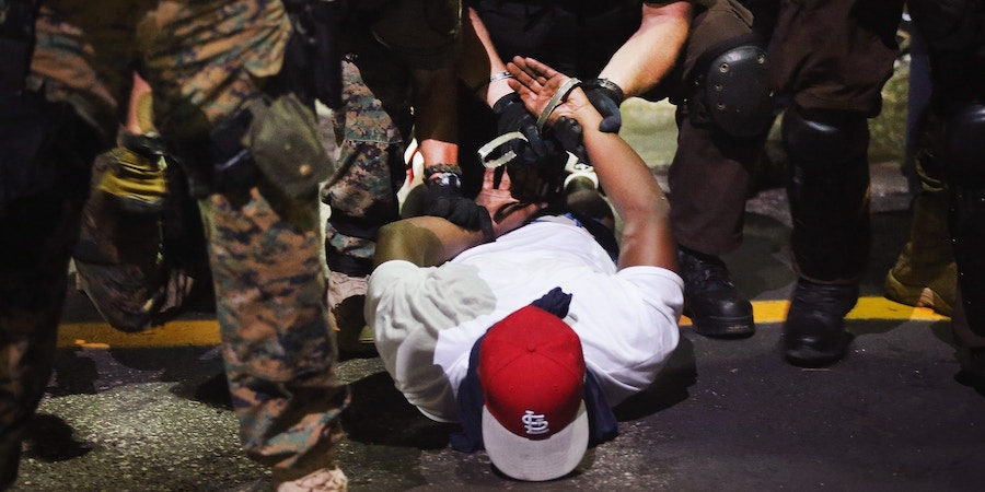 FERGUSON, MO - AUGUST 19:  Police arrest a demonstrator protesting the killing of teenager Michael Brown on August 19, 2014 in Ferguson, Missouri. Brown was shot and killed by a Ferguson police officer on August 9. Despite the Brown family's continued call for peaceful demonstrations, violent protests have erupted nearly every night in Ferguson since his death.  (Photo by Scott Olson/Getty Images)