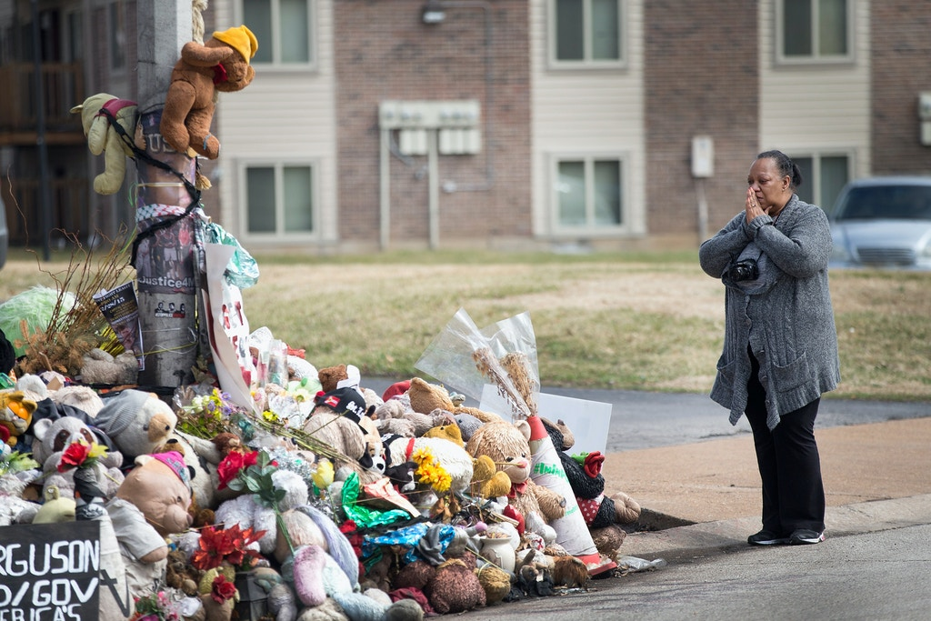 FERGUSON, MO - MARCH 14:  Mia Swisher says a prayer during a visit to a memorial to Michael Brown outside the Canfield Green apartments where he was shot and killed by a police officer last August on March 14, 2015 in Ferguson, Missouri.  The town of Ferguson has experienced many protests, which have often been violent, since Brown's death. On Wednesday evening two police officers were shot while they were securing the Ferguson police station during a protest.  (Photo by Scott Olson/Getty Images)