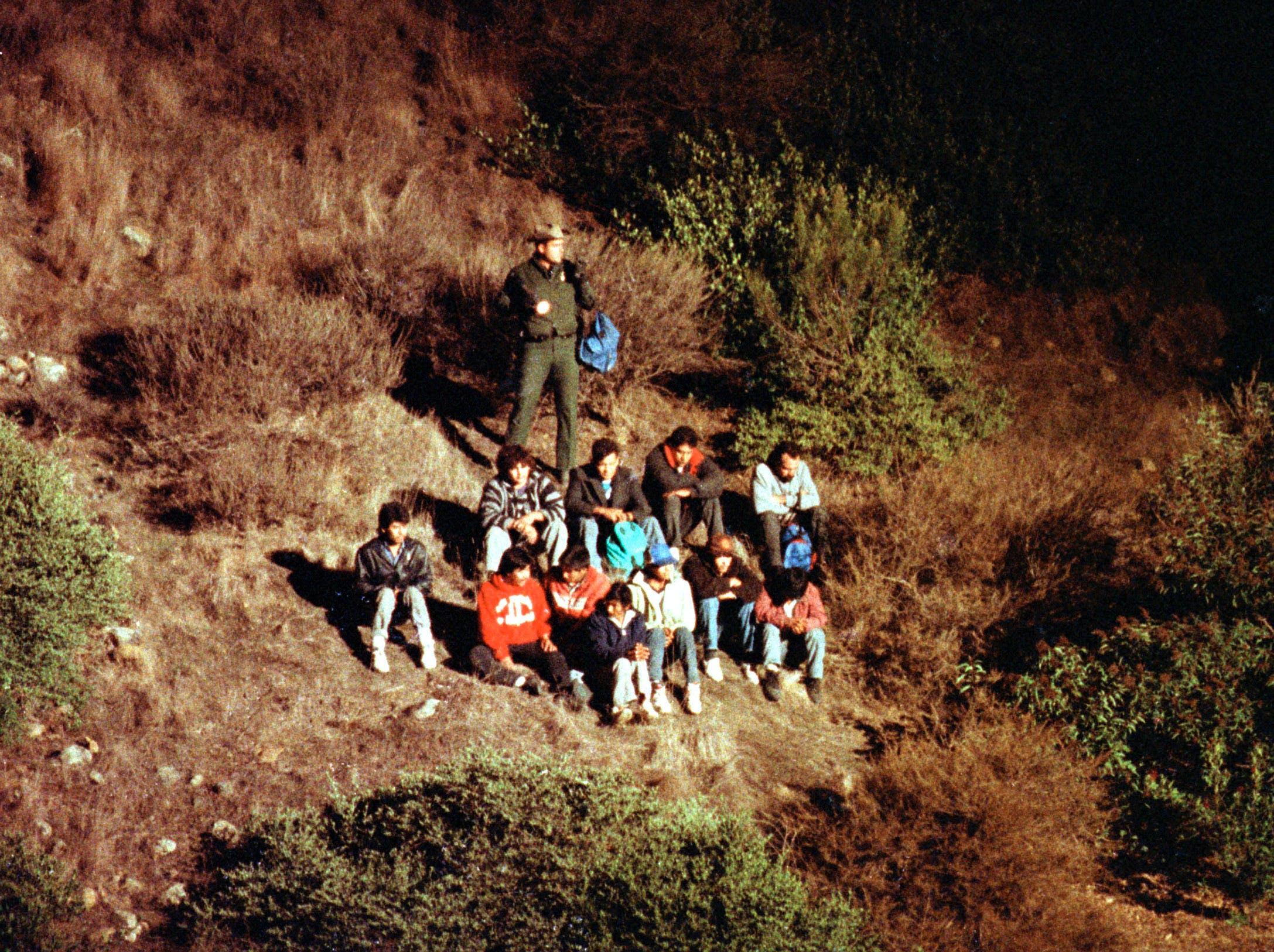 Imigrantes mexicanos são revistados pela Patrulha de Fronteira dos EUA numa íngreme encosta de cânion, iluminada por um helicóptero da Patrulha de Fronteira.