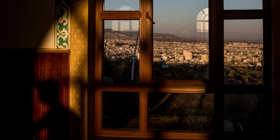 KILIS, TURKEY - MARCH 01: The town of Kilis is seen through the window of the Muhammed Bedevi Mosque on March 1, 2016 in Kilis, Turkey. Kilis a city located just 10km from the Syrian border and the location of the Oncupinar Border crossing, has been Turkey's frontline during the refugee crisis. With a population of 129,000 Kilis was recently nominated for the Nobel Peace Prize after the number of refugees living in the city equalled that of the Turkish population. How the city has integrated this number of refugees and the support given to refugees newly arrived, has not been seen in other cities around the world. The city has made considerable efforts to integrate the refugees by allowing them to work, rent apartments and open businesses such as cafe's and Syrian restaurants, the town has seen a massive boom in construction as it builds cheap new apartment blocks in an attempt to provide affordable housing for the refugees allowing them to have a standard of living similar to what they had in Syria.  (Photo by Chris McGrath/Getty Images)