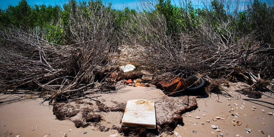 A grave stone rests on the beach where a cemetery once stood but has been washed away due to erosion in an area called Canaan in Tangier, Virginia, May 16, 2017, where climate change and rising sea levels threaten the inhabitants of the slowly sinking island.Now measuring 1.2 square miles, Tangier Island has lost two-thirds of its landmass since 1850. If nothing is done to stop the erosion, it may disappear completely in the next 40 years. / AFP PHOTO / JIM WATSON (Photo credit should read JIM WATSON/AFP/Getty Images)