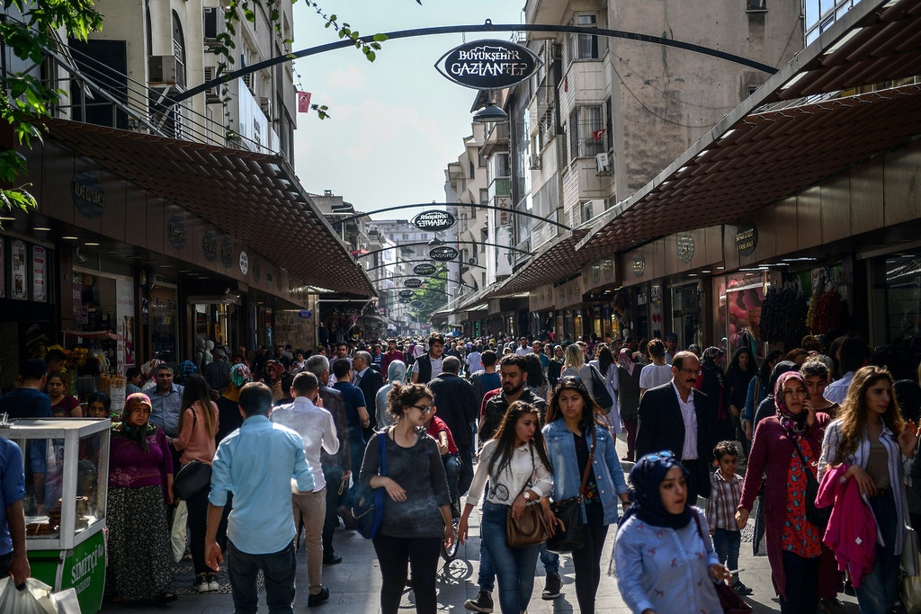 Pedestrians walk on a shopping street in Gaziantep, in the south-west province of Turkey on May 1, 2018. - In the Turkish city of Gaziantep, home to around half a million Syrians who fled the civil war south of the border, hundreds of Syrian businesses are thriving in a boost both for the displaced community and their host country. (Photo by OZAN KOSE / AFP)        (Photo credit should read OZAN KOSE/AFP/Getty Images)