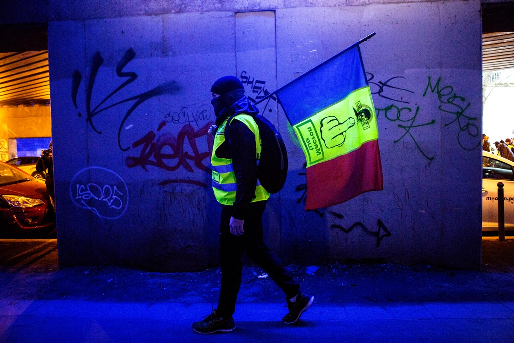 "A Gilet Jaune protester carries a French flag with the words ""Macron kills"" written on it in Paris, France, January 12, 2018. Joe Penney for The Intercept"