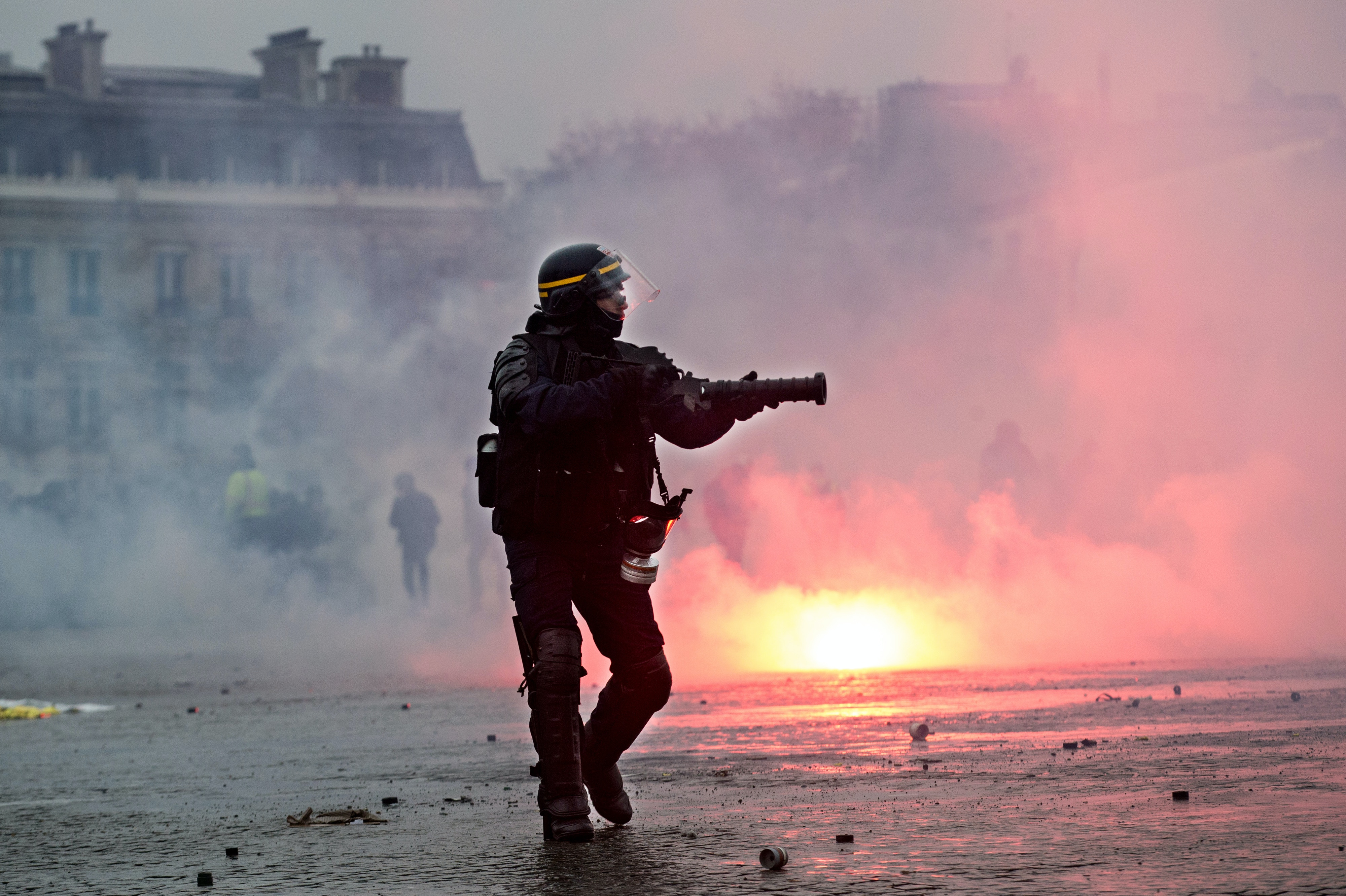 A riot police officer fires tear gas canisters at Gilet Jaune protesters in Paris, France, January 12, 2018. Joe Penney for The Intercept