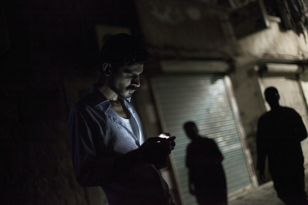 Homem sírio olha para o seu celular no bairro de Bustan al-Qasr, em Aleppo, Síria, em 21 de setembro de 2012.