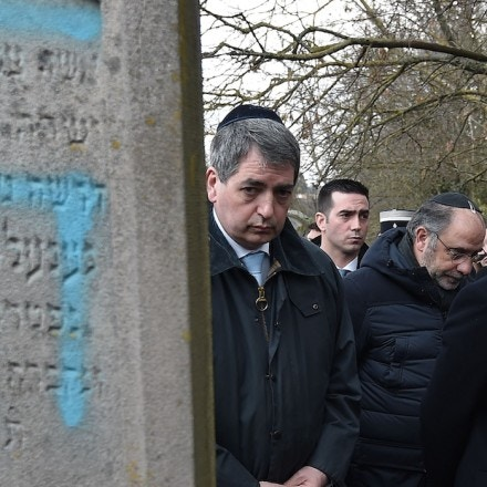 TOPSHOT - French President Emmanuel Macron looks at a grave vandalised with a swastika during a visit at the Jewish cemetery in Quatzenheim, on February 19, 2019, on the day of a nationwide marches against a rise in anti-Semitic attacks. - Around 80 graves have been vandalised at the Jewish cemetery in the village of Quatzenheim, close to the border with Germany in the Alsace region, which were discovered early February 19, 2019, according to a statement from the regional security office. (Photo by Frederick FLORIN / POOL / AFP)        (Photo credit should read FREDERICK FLORIN/AFP/Getty Images)