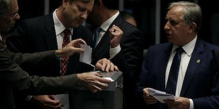 Senadores colocam cédulas de votação no triturador de papel após suspeita de fraude no processo de votação.