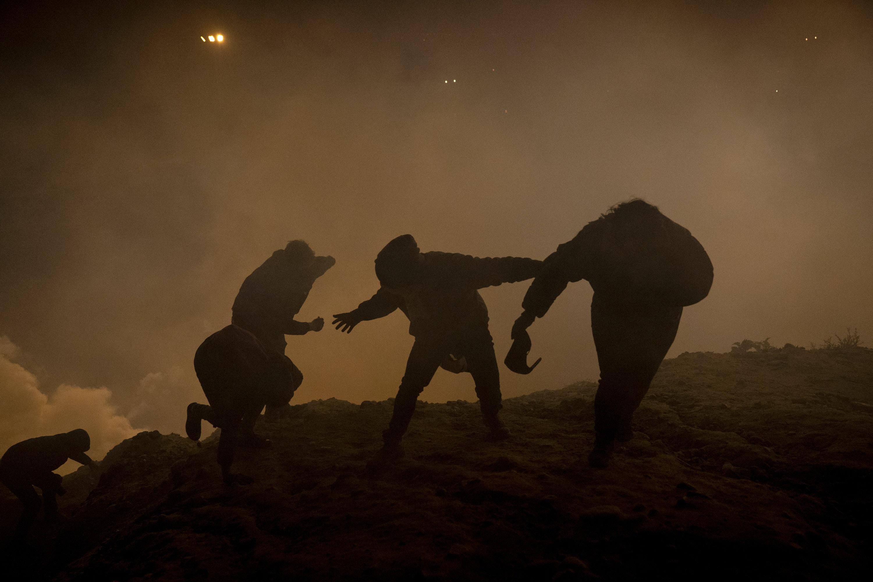 Migrants, journalists and U.S. activists run from tear gas on January 1, 2019 after US authorities fired tear gas over the border wall in Tijuana, Mexico. A group of approximately 150 migrants attempted to cross the border but their attempt was thwarted when CBP discovered where they were hiding and used several crowd control techniques to disperse the group.Photo by Kitra Cahana / MAPS