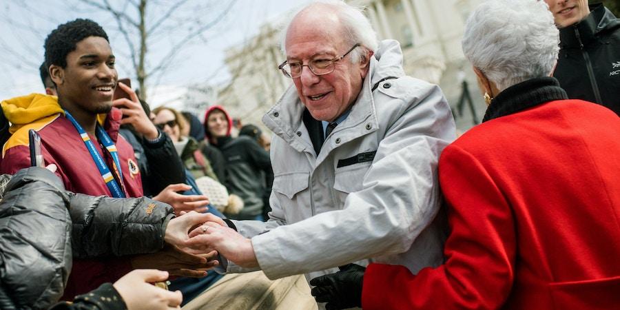 O senador Bernie Sanders e a deputada Grace Napolitano cumprimentam alunos enquanto participam de um comício no Capitólio, em Washington, DC, em 14 de março de 2018.