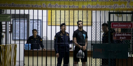 Bahraini football player Hakeem al-Araibi, center, stands to be transferred to a jail in a court house in Bangkok, Thailand, Tuesday, Dec. 11, 2018. A Thai court has ruled that the soccer player who holds refugee status in Australia can be held for 60 days pending the completion of an extradition request by Bahrain, the homeland he fled four years ago on account of alleged political persecution. (AP Photo/Gemunu Amarasinghe)