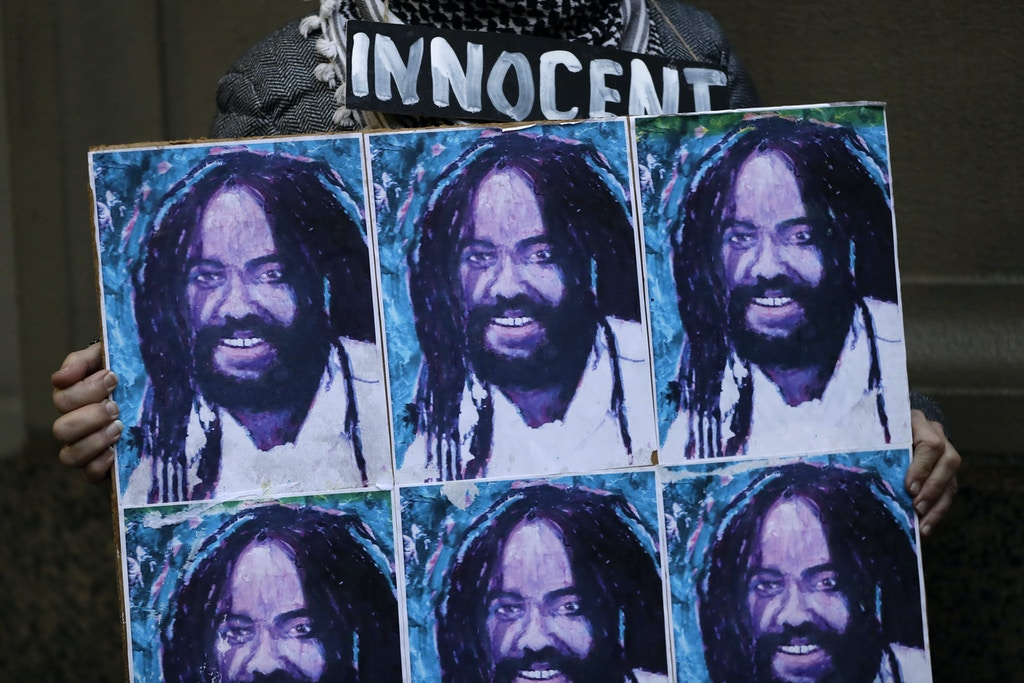 A protestor holds up a poster depicting Mumia Abu-Jamal during a demonstration outside the offices of District Attorney Larry Krasner, Friday, Dec. 28, 2018, in Philadelphia. A judge issued a split ruling Thursday that grants Abu-Jamal another chance to appeal his 1981 conviction in a Philadelphia police officer's death. (AP Photo/Matt Slocum)