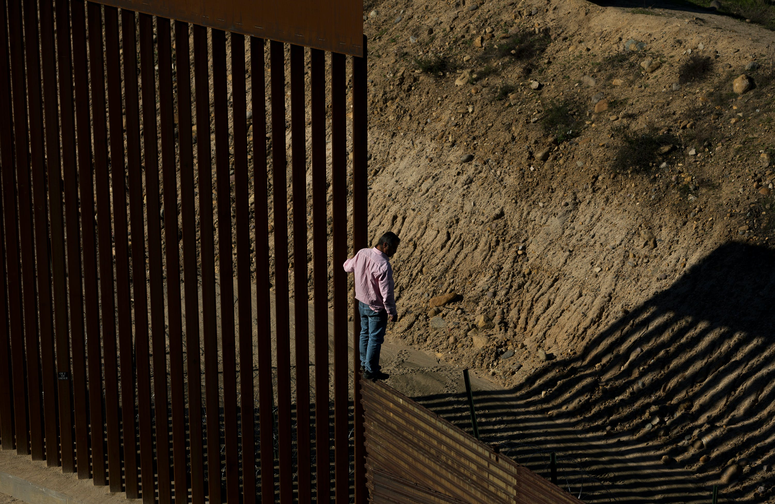 A migrant stands on the border fence before jumping to get into the U.S. side to San Diego, Calif., from Tijuana, Mexico, Friday, Dec. 28, 2018. Discouraged by the long wait to apply for asylum through official ports of entry, many migrants from recent caravans are choosing to cross the U.S. border wall and hand themselves in to border patrol agents. (AP Photo/Daniel Ochoa de Olza)