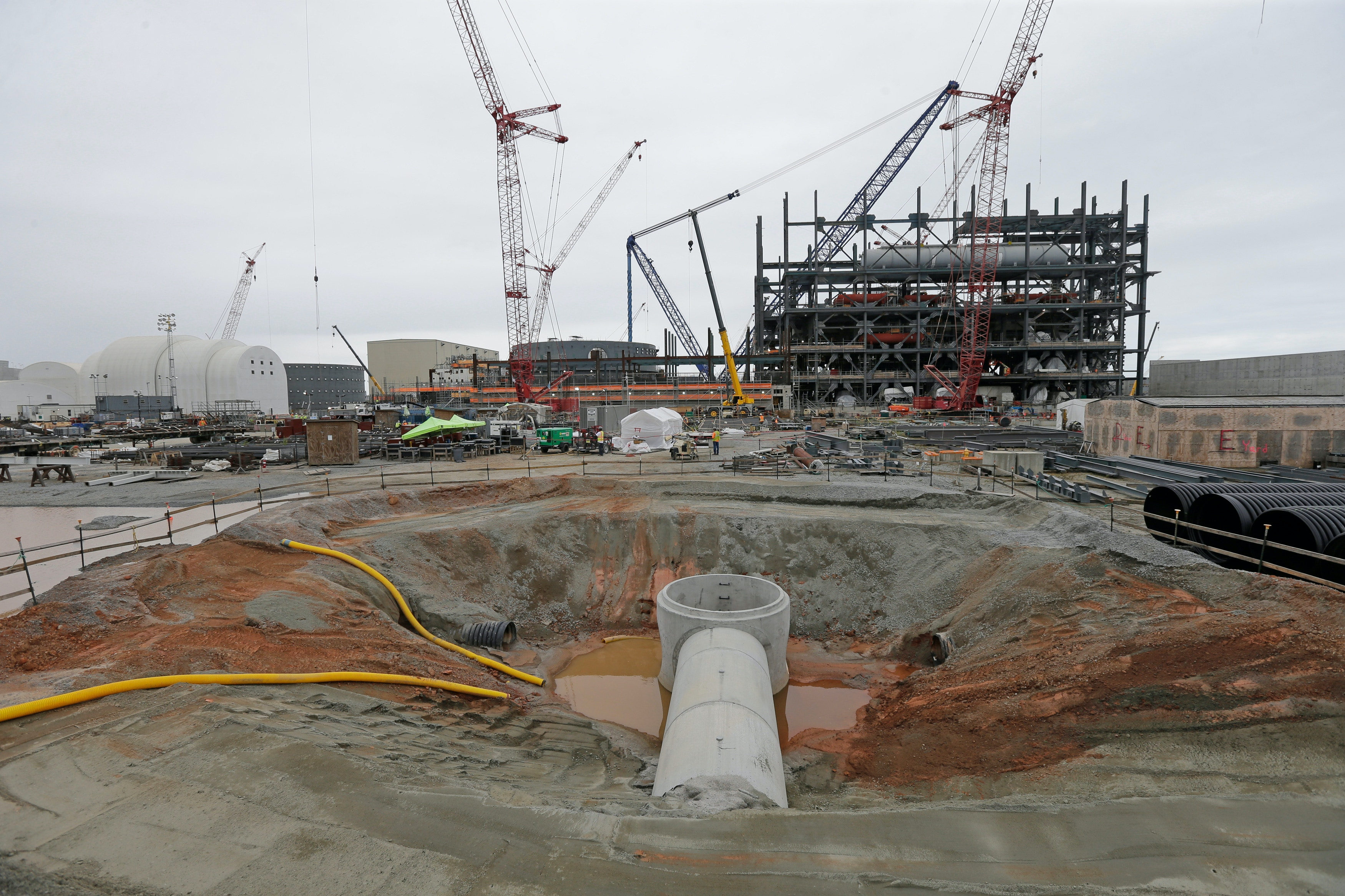 V.C. Summer Nuclear Station's unit two's turbine, right, and containment unit, center, are shown under construction near Jenkinsville, S.C., during a media tour of the facility Wednesday, Sept. 21, 2016.  SCE&G is seeking a 3.1 percent residential raise that would be the largest single rate increase since the utility began charging its 700,000 customers for the reactors' construction. The hike, which would take effect at the end of November if approved, would be the ninth such increase to pay for the $14 billion reactors since 2009. (AP Photo/Chuck Burton)