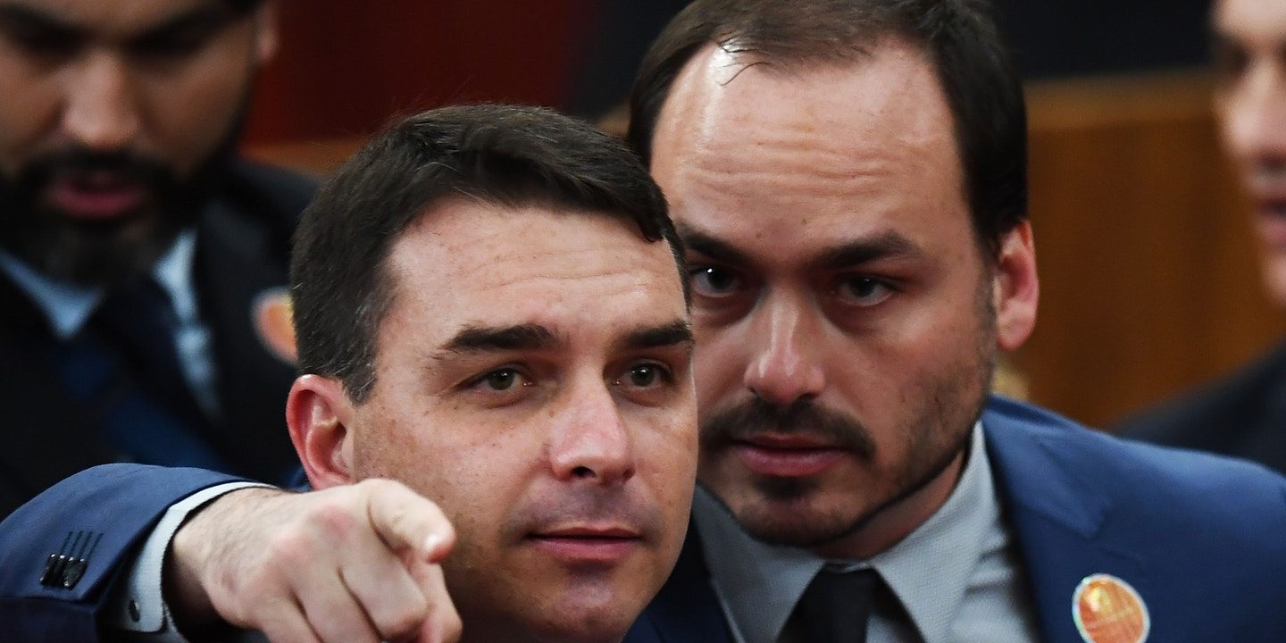 Brazilian Senator for Rio de Janeiro Flavio Bolsonaro (L) and Councillor of Rio de Janeiro Carlos Bolsonaro attend their father Brazilian President-elect Jair Bolsonaro's ceremony to receive a diploma that certifies he can take office as president, at the TSE in Brasilia, on December 10, 2018. - Bolsonaro takes office on January 1, 2019. (Photo by EVARISTO SA / AFP)        (Photo credit should read EVARISTO SA/AFP/Getty Images)