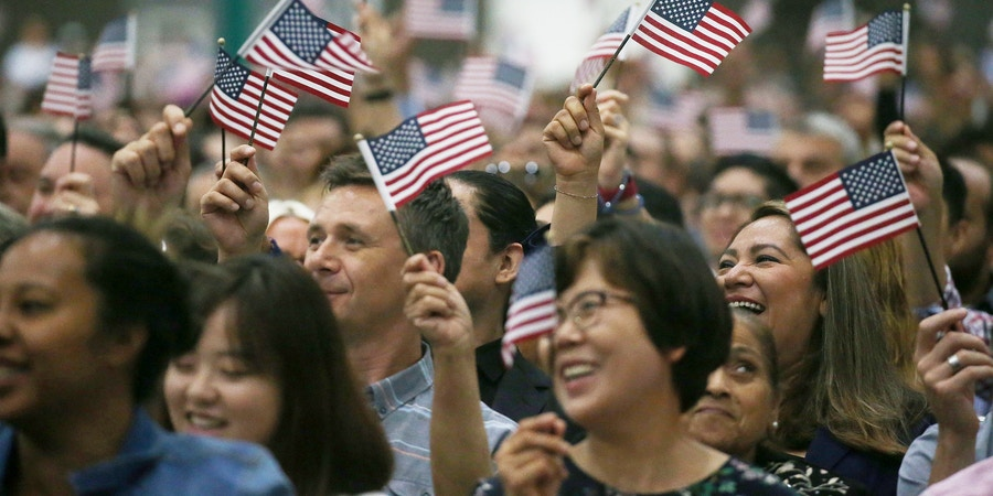 LOS ANGELES, CA - JULY 25: People wave American flags at a naturalization ceremony on July 25, 2018 in Los Angeles, California. Two naturalization ceremonies held today at the Los Angeles Convention Center are expected to welcome more than 8,800 immigrants from 128 countries who took the citizenship oath and pledged allegiance to the American flag. During FY 2016, the United States welcomed 752,800 new citizens to the country.  (Photo by Mario Tama/Getty Images)
