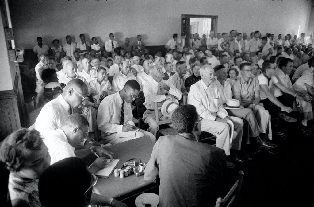 Interior view of the segregated seating in the packed Tallahatchie County Courthouse during the trial of J W Milam and Roy Bryant who were accused of the murder of Emmett Till, Sumner, Mississippi, September 1955. Till was a 14-year-old African-American boy from Chicago who had allegedly flirted with Bryant's wife, a white woman. Photojournalist Ernest Withers of the Chicago Defender is seated in center foreground with his back to the camera. (Photo by Ed Clark/The LIFE Picture Collection/Getty Images)  Ernest Withers (back to camera)