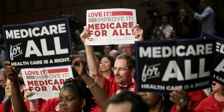 WASHINGTON, DC - SEPTEMBER 13:  Supporters of U.S. Sen. Bernie Sanders (I-VT) hold signs during an event on health care September 13, 2017 on Capitol Hill in Washington, DC. Sen. Sanders held an event to introduce the Medicare for All Act of 2017.  (Photo by Alex Wong/Getty Images)