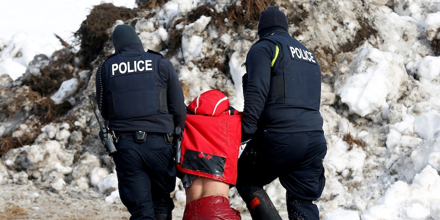Police detain Ricardo Salazar, 25, of San Bernardino, California, in the main opposition camp against the Dakota Access oil pipeline near Cannon Ball, North Dakota, U.S., February 23, 2017. REUTERS/Terray Sylvester - RC122B1745B0