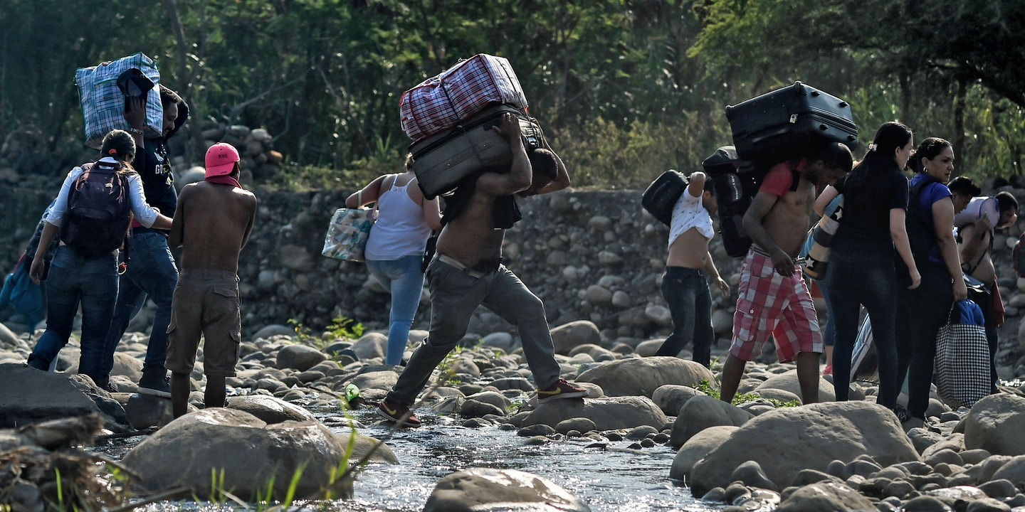 "People taking irregular roads cross the Tachira river from Cucuta in Colombia to San Antonio del Tachira in Venezuela, near the Simon Bolivar international Bridge, on February 25, 2019. - United States Vice President Mike Pence told Venezuelan opposition leader Juan Guaido that Donald Trump supports him ""100 percent"" as the pair met regional allies on Monday to thrash out a strategy to remove Nicolas Maduro from power after the failed attempt to ship in humanitarian aid. (Photo by Luis ROBAYO / AFP) (Photo credit should read LUIS ROBAYO/AFP/Getty Images)"