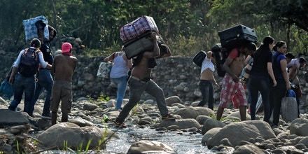 People taking irregular roads cross the Tachira river from Cucuta in Colombia to San Antonio del Tachira in Venezuela, near the Simon Bolivar international Bridge, on February 25, 2019. - United States Vice President Mike Pence told Venezuelan opposition leader Juan Guaido that Donald Trump supports him