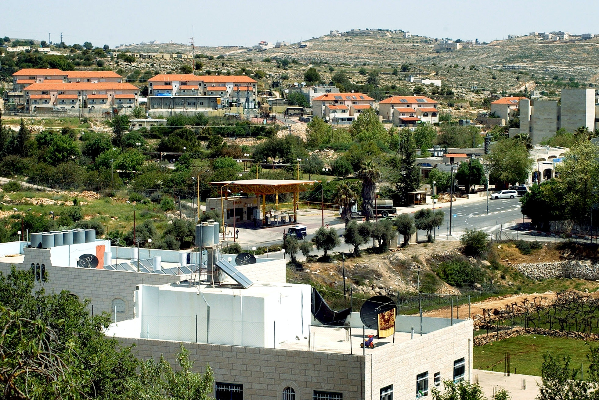 "This is a partial view of the southern West Bank Jewish settlement of Kiryat Arba, adjacent to the Palestinian city of Hebron, Tuesday April 13, 2004. In the foreground there are Palestinians houses in Hebron, and in the hilltops, background, there are closeby Palestinian villages. Israeli Prime Minister Ariel Sharon disclosed the final element of his ""disengangement"" plan late Monday just hours before his departure for the United States, naming for the first time the West Bank areas he plans to keep under Israeli control, including the Kiryat Arba settlement. (AP Photo/Nasser Shiyoukhi)"