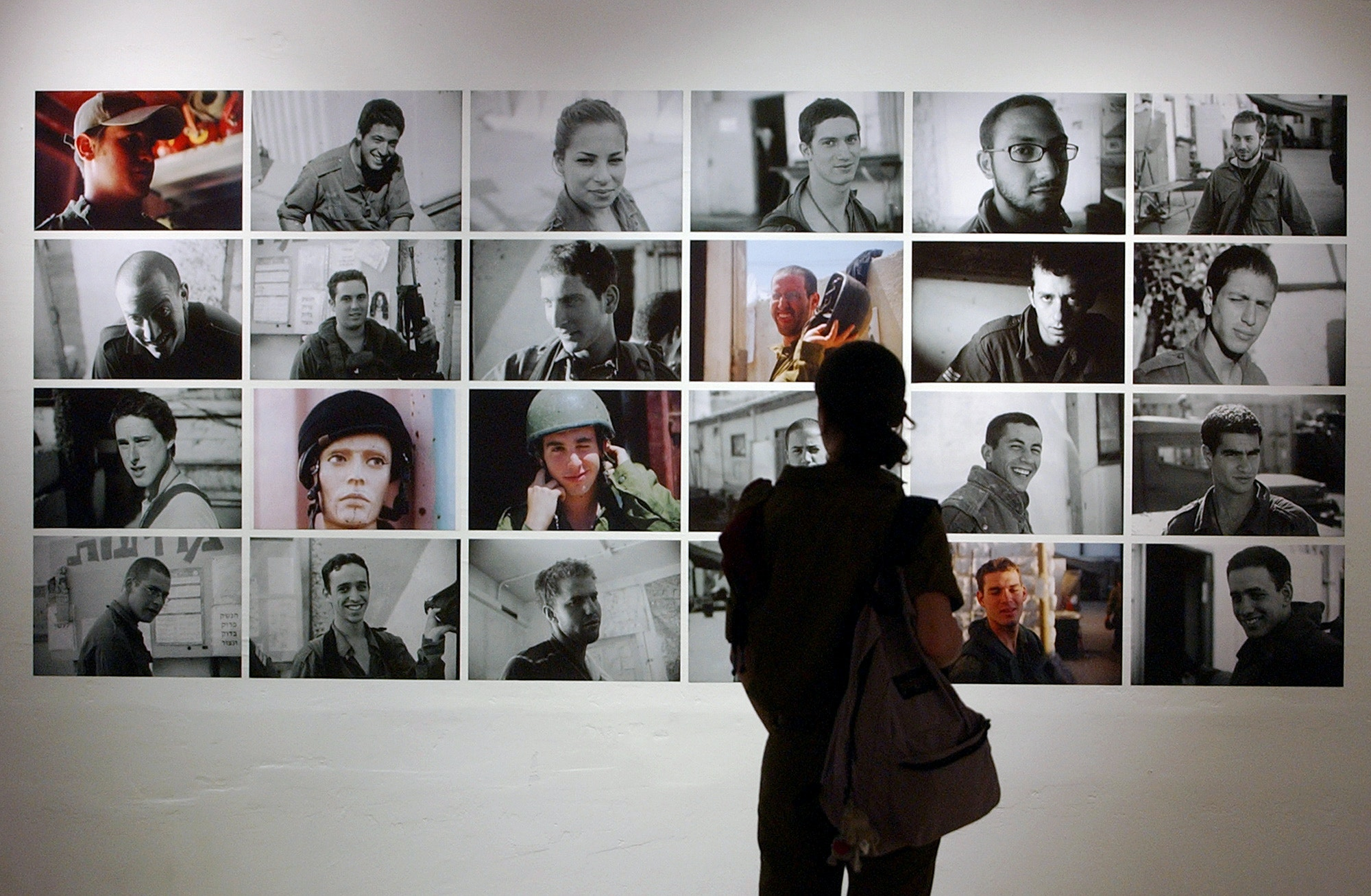 "An Israeli soldier, visiting the ""Breaking the Silence"" exhibition, looks at photos taken by Israeli soldiers during their military service in the Palestinian southern West Bank city of Hebron, on display in Tel Aviv, Israel, Wednesday, June 23, 2004. The Israeli army interrogated on Wednesday five reserve  soldiers who set up a photo exhibit giving vivid accounts of abuse and  harassment of Palestinians in Hebron, the manager of the gallery displaying the  exhibit said, a day after the army and policeraided the exhibit, and confiscated an album of newspaper clippings and  a videotape of testimony from more than 70 soldiers. (AP Photo/Ariel Schalit)"