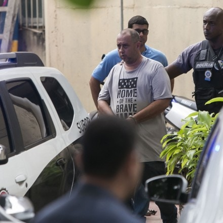 Suspect and former police officer Elcio Vieira de Queiroz, who is under arrest for the murder of councilwoman Marielle Franco and her driver, is escorted by police officers, in Rio de Janeiro, Brazil, March 14, 2019. Franco and her driver, Anderson Gomes, were gunned down in central Rio on the evening of March 14, 2018. De Queiroz allegedly drove a car involved in the shooting. (AP Photo/Bruna Prado)