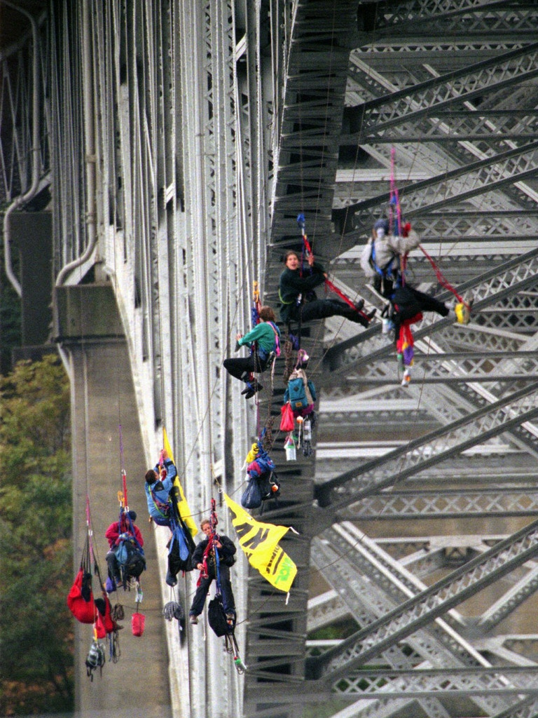 Seven Greenpeace demonstrators slowly make their way up ropes Monday, Aug. 18, 1997, toward the deck of Seattle's Aurora Bridge after being suspended for two days to protest factory trawler fishing. The seven, plus another who had been under the bridge deck monitoring the lines, were placed under arrest on charges of reckless endangerment. The five women and two men rappelled over the side of the bridge Saturday morning and strung ropes in an attempt to block two trawlers attempting to depart Lake Union on their way to pollock fishing grounds in the Bering Sea. (AP Photo/Elaine Thompson)