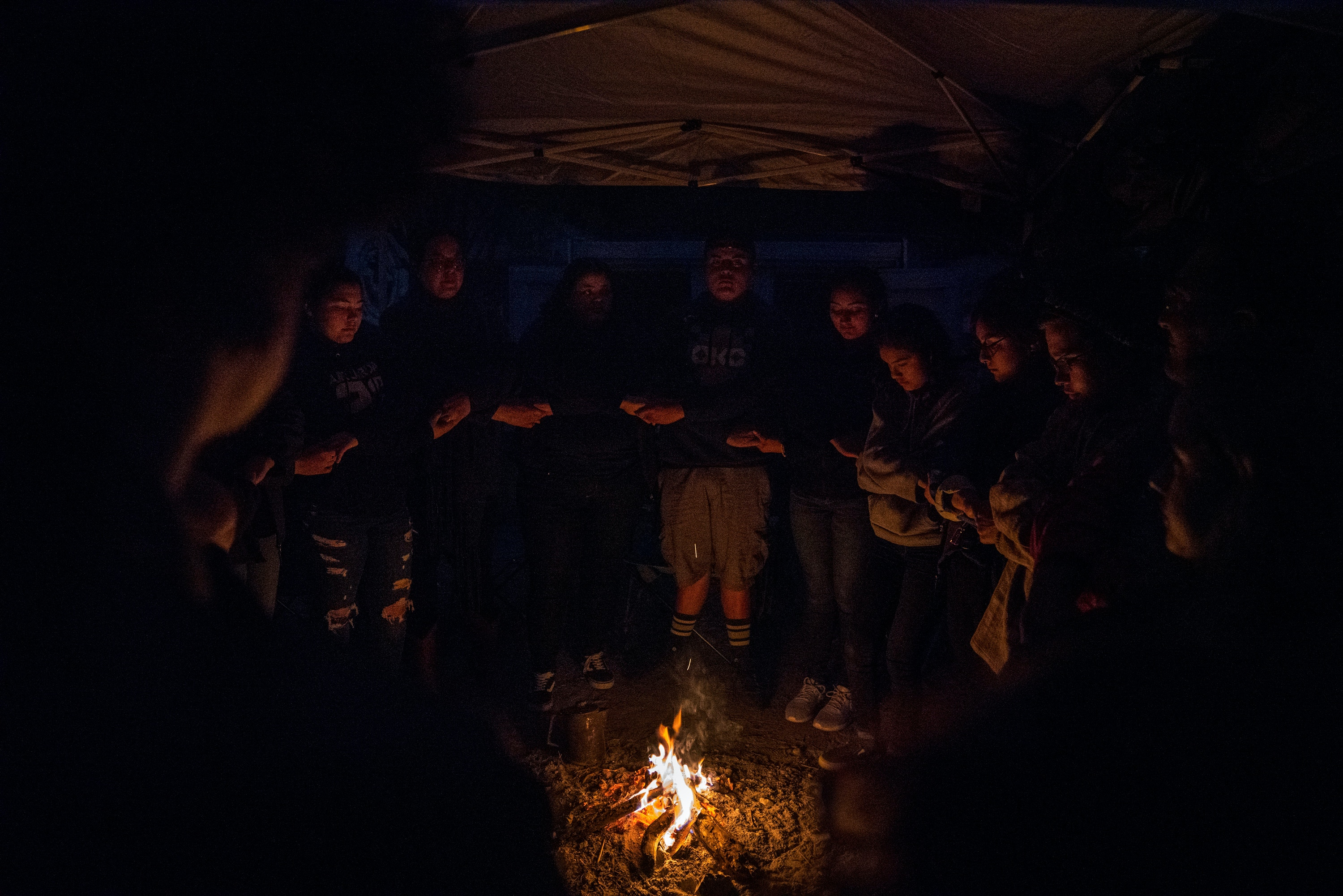"""Al Exito"" members along with Carrizo/Comecrudo Tribe members, and activists gather around the fire to share things that they are thankful for at Yalui Village in Hidalgo County, Texas on March 17, 2019.Photo: Verónica G. Cárdenas for The Intercept"